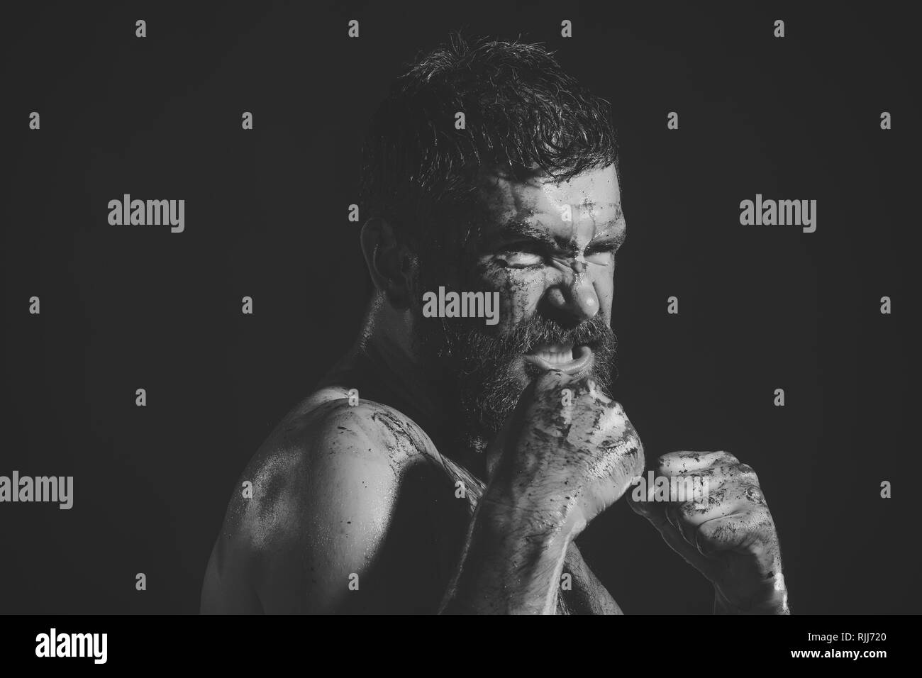 Bearded hipster with blood paint on angry face - Stock Image