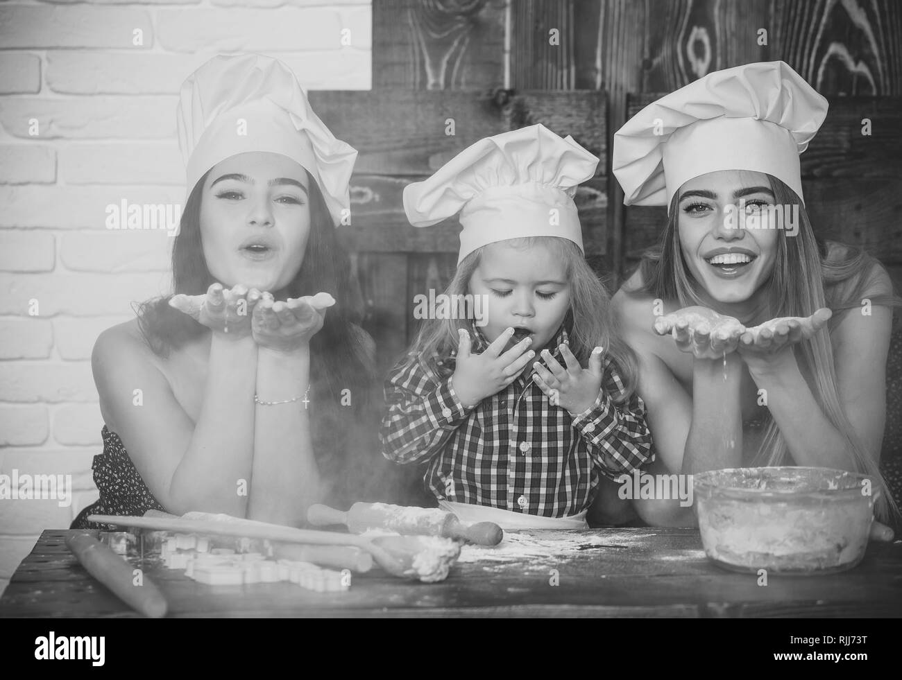 Child and women blowing flour - Stock Image