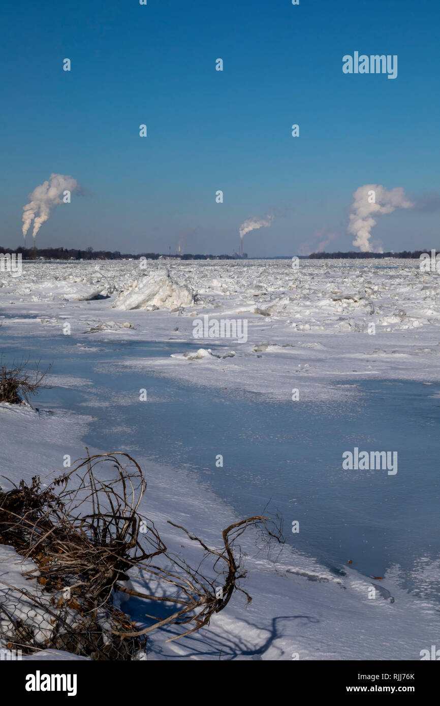 Marine City, Michigan - DTE Energy coal-fired power plants line the U.S. side (left) of the ice-filled St. Clair River. The Canadian side has mostly r - Stock Image