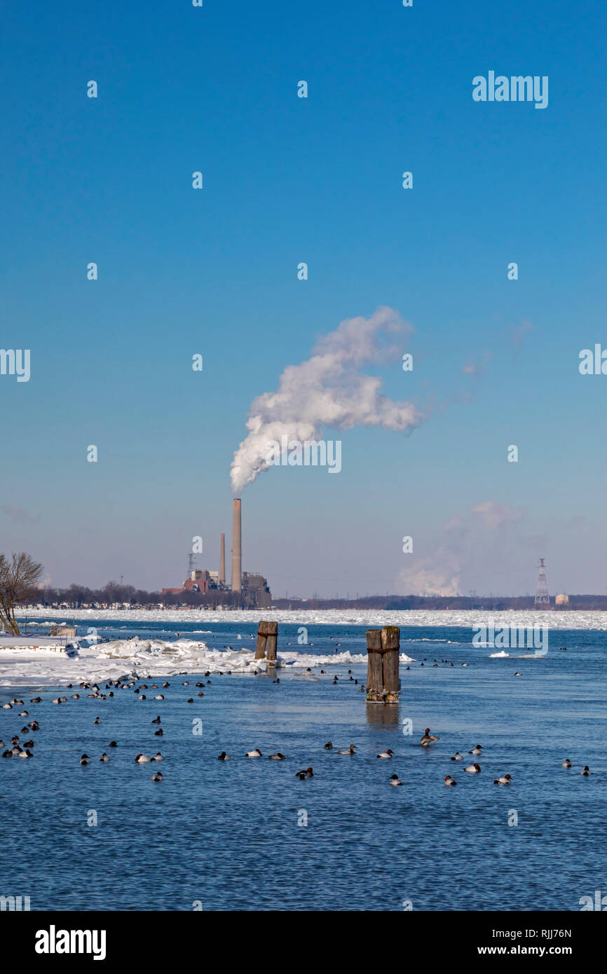 Marine City, Michigan - DTE Energy's coal-fired St. Clair power plant on the U.S. side of the ice-filled St. Clair River. Canvasback ducks swim in ope - Stock Image