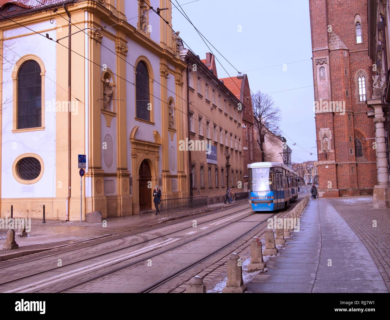 Wintry landscape with snow on the ground and electric train or tram passing. Stock Photo