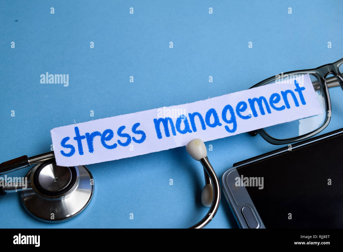 Conceptual image with Stress management inscription with the view of stethoscope, eyeglasses and smartphone on the blue background. Medical Conceptual - Stock Image