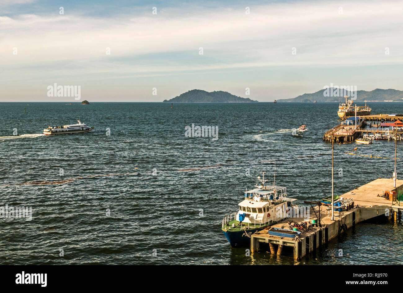 Boats in South China sea off Kota Kinabalu Sabah Malaysia Borneo during the day and at sunset. Also ferries going to and from Island off Kota Kinabalu - Stock Image