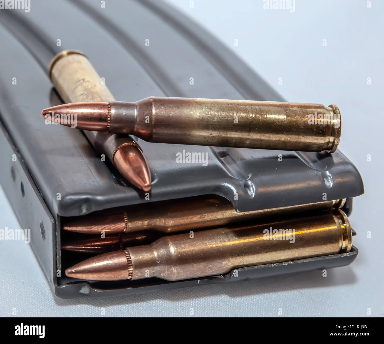 A rifle magazine loaded with 223 caliber bullets with two separate bullets on top of it on a white background - Stock Image