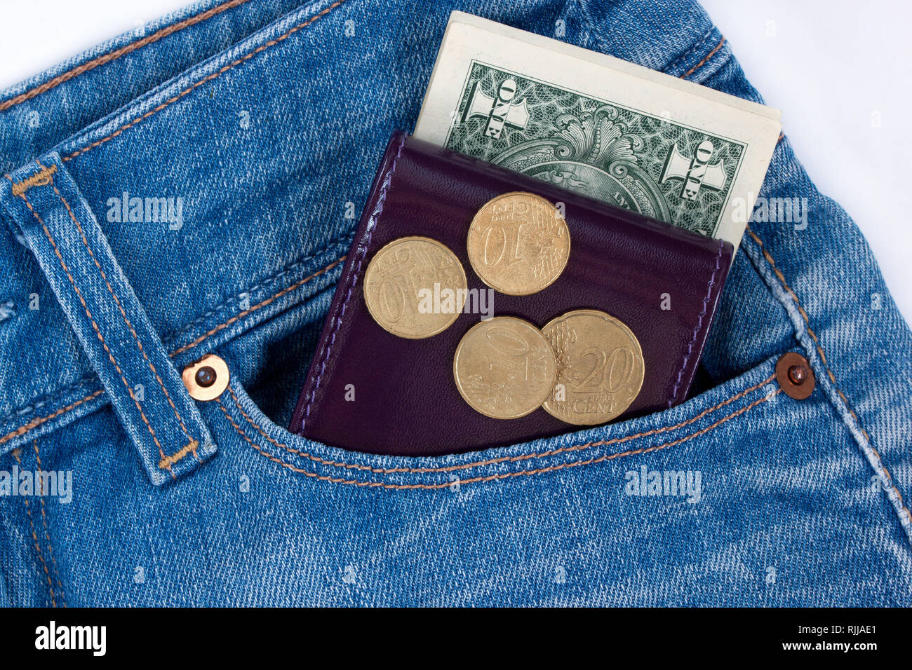 Wallet and ready money are lying in side pocket of blue jeans. Modern lifestyle. - Stock Image