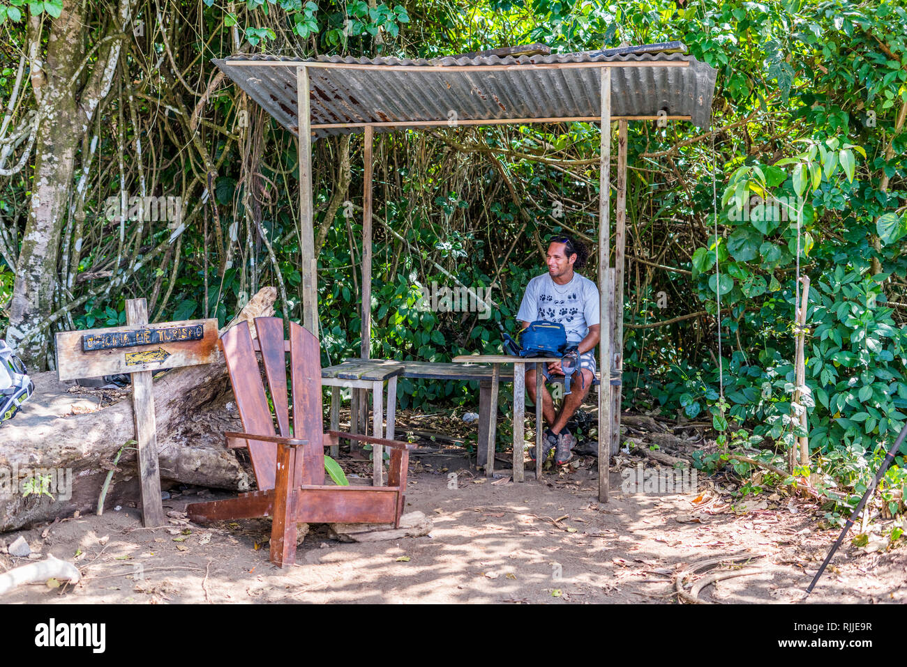 A photo of a man sitting in the modest office of tourism at the entrance to the beautiful and unique Corcovado National Park in Costa Rica - Stock Image