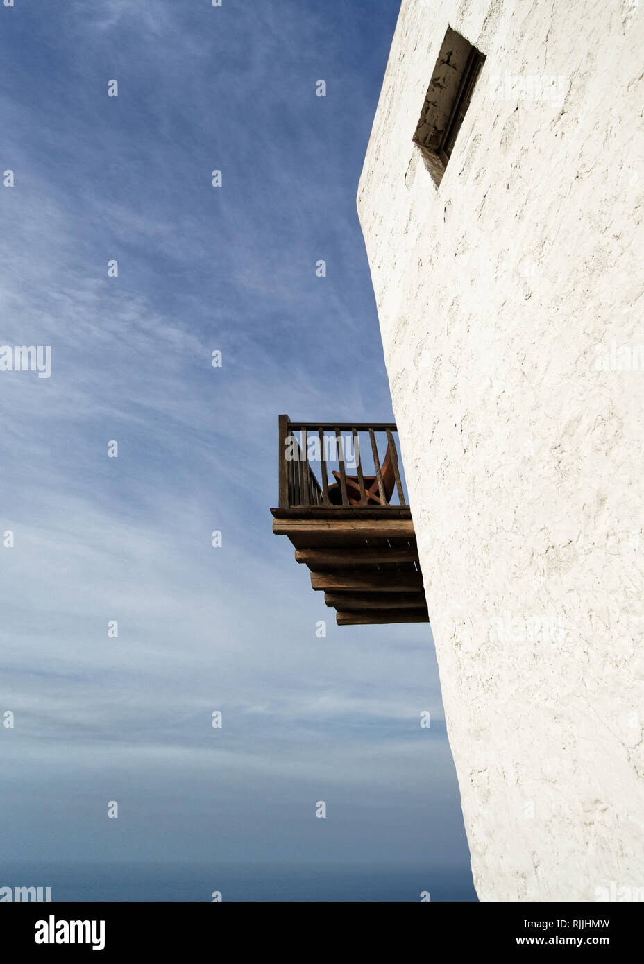 Perspective view from below of an older white typical building with a wooden balcony and a window, in the background the ocean and blue sky - Location - Stock Image
