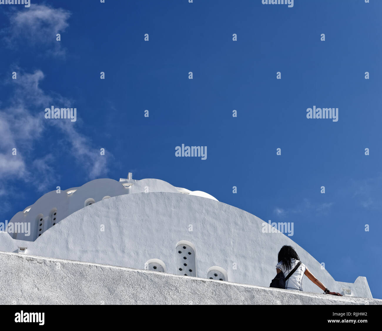 Perspective view from below of an older white typical building, in front of it a person in typical attitude for tourists, blue sky - Location: Greece, - Stock Image