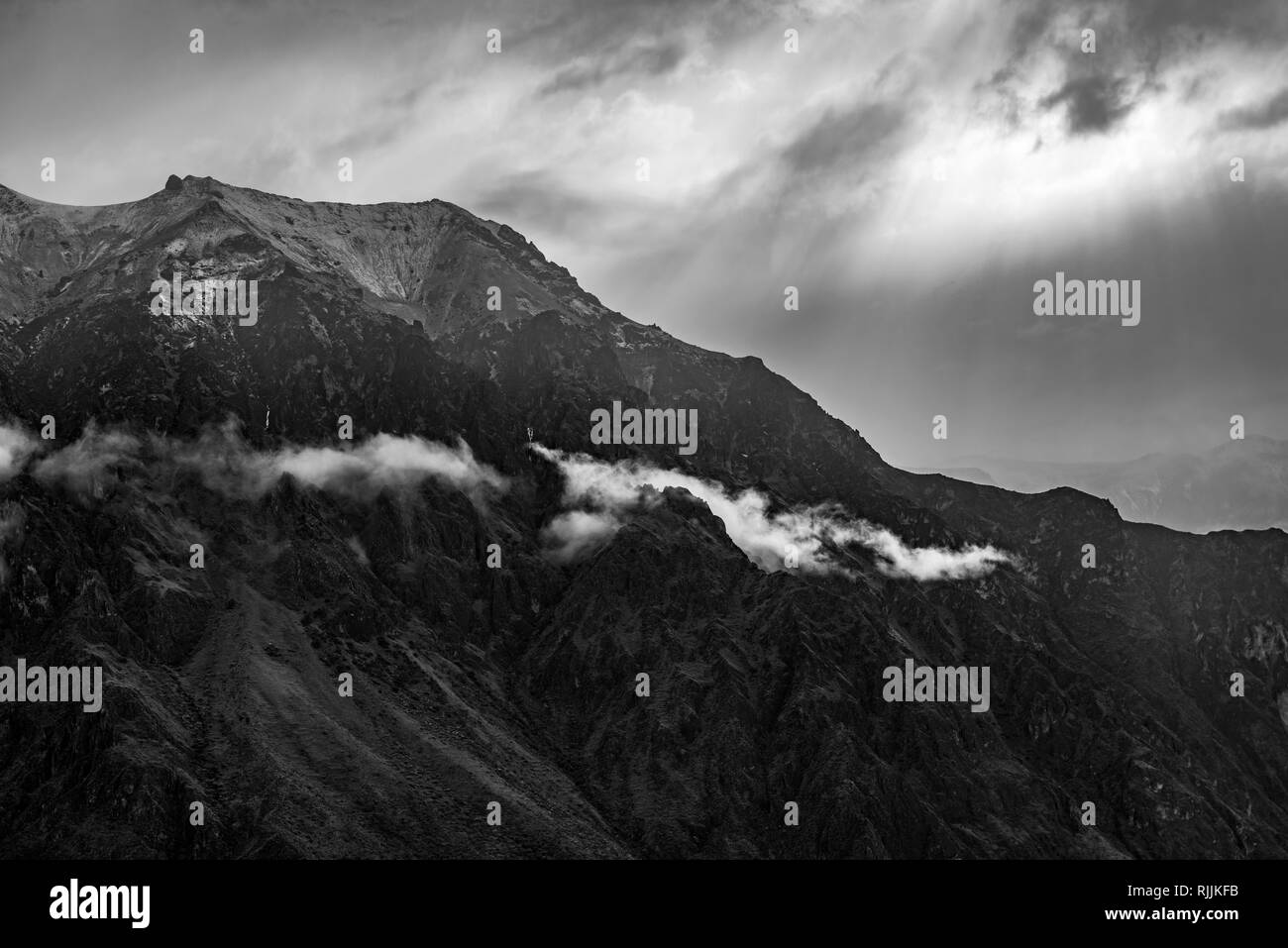 The Andes mountain range in black and white as sunlight illuminates the peaks and clouds near the Colca Canyon, Arequipa, Peru. - Stock Image