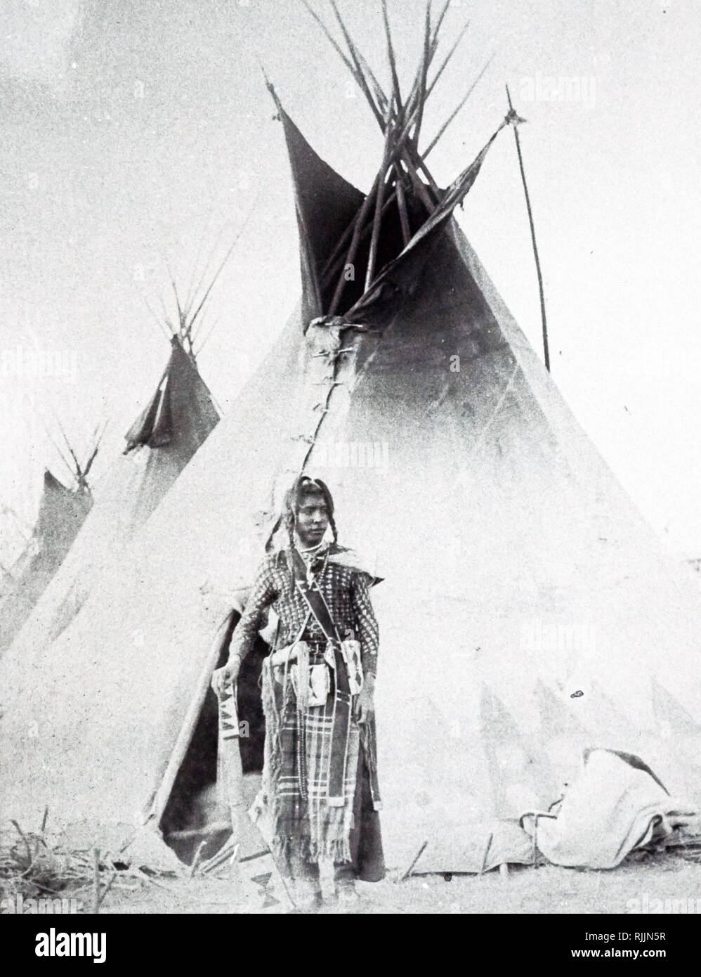 A photograph of a young 'Black Foot' Indian outside his tent. Dated 19th century - Stock Image