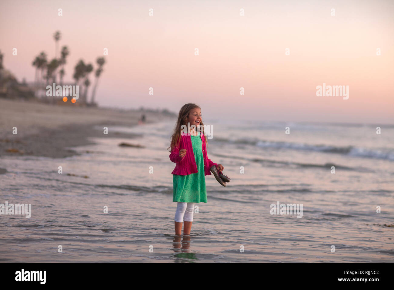 Little girl looking out at the ocean in excitement Stock Photo