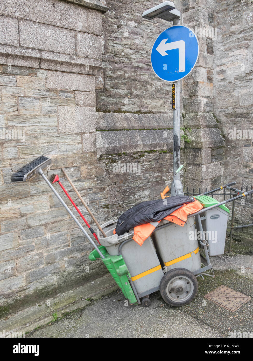 Street cleaner's trolley cart pulled up beside Turn Left road sign. Stock Photo