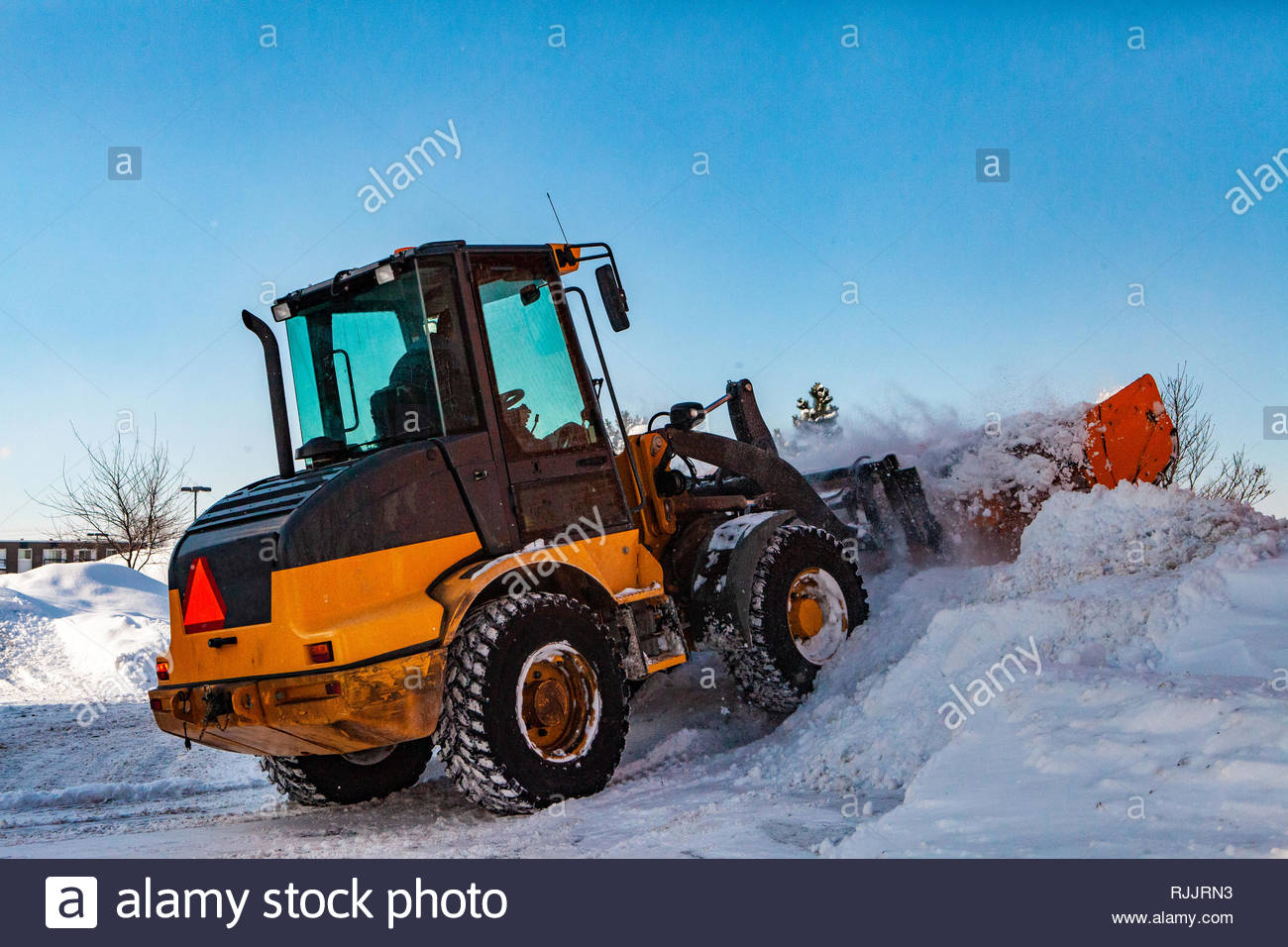 Snowplow tractor clearing snow. Yellow tractor making a pile of snow while clearing the streets after a winter storm - Stock Image