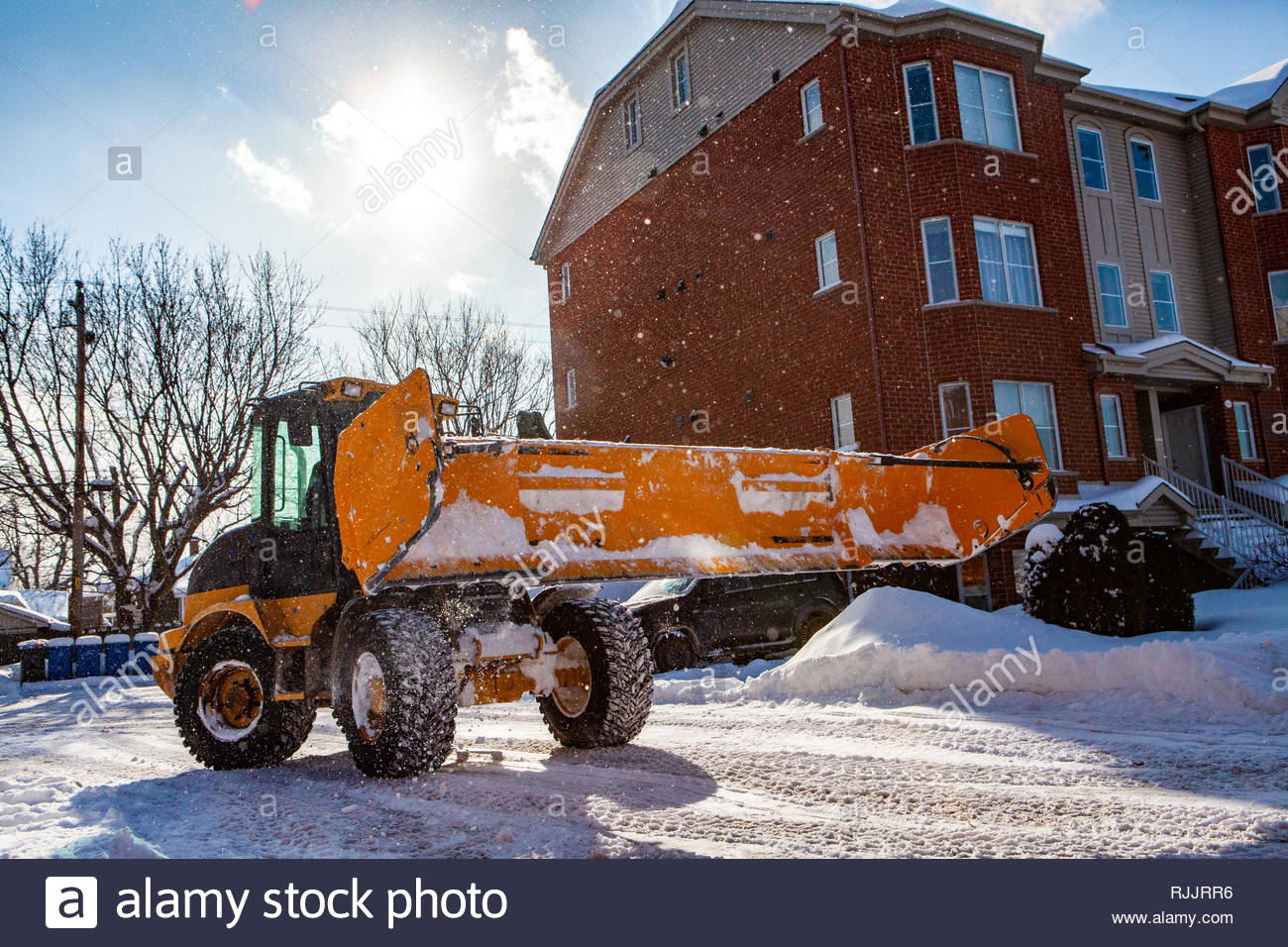 Snowplow tractor clearing snow. Wide view of yellow snowplow clearing the streets after a snow storm, snowflakes in the air on a sunny day - Stock Image
