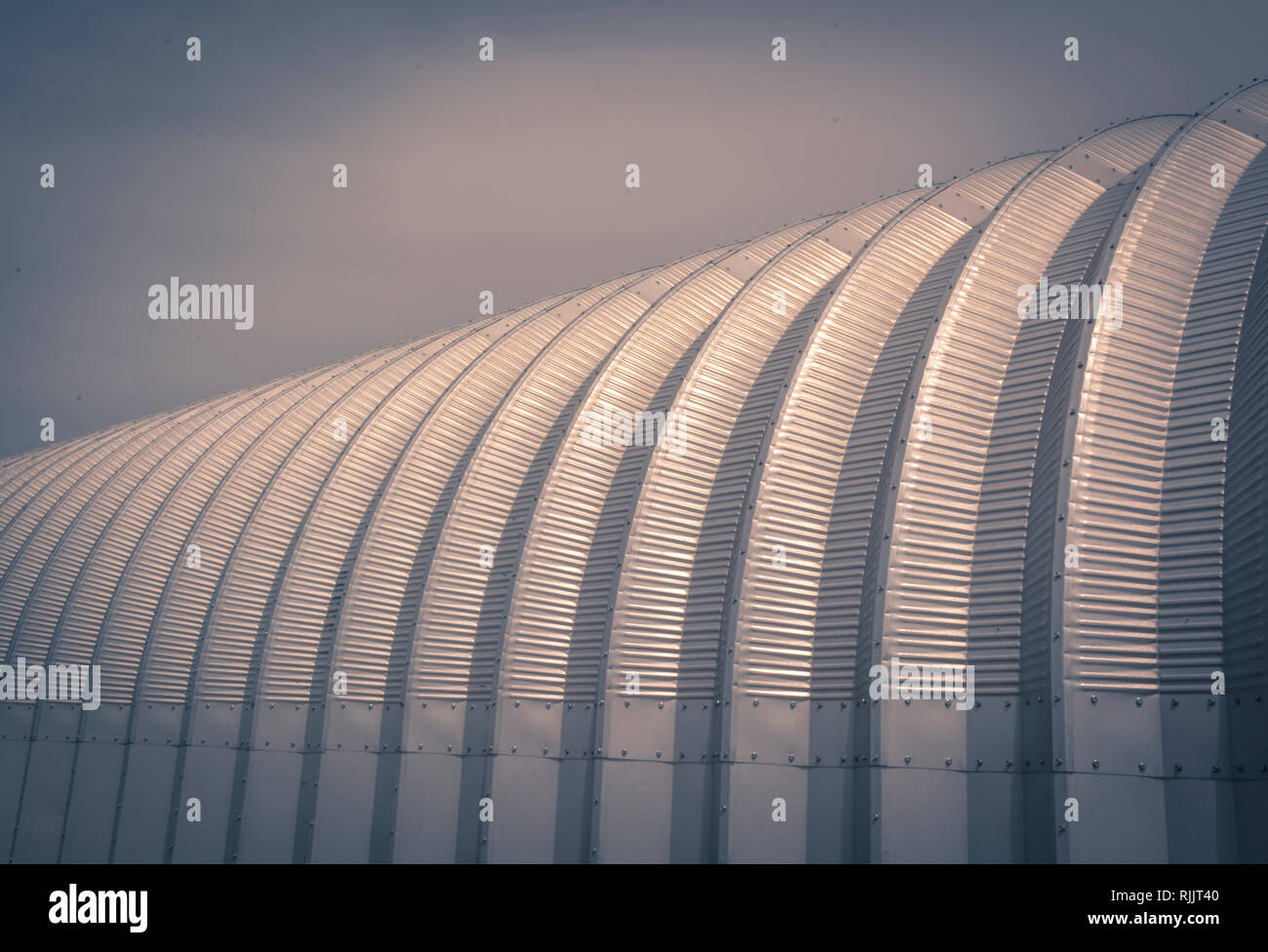 A conceptual background and artistic feeling to a close-up of a half round metal agricultural building outside of Amarillo TX Stock Photo