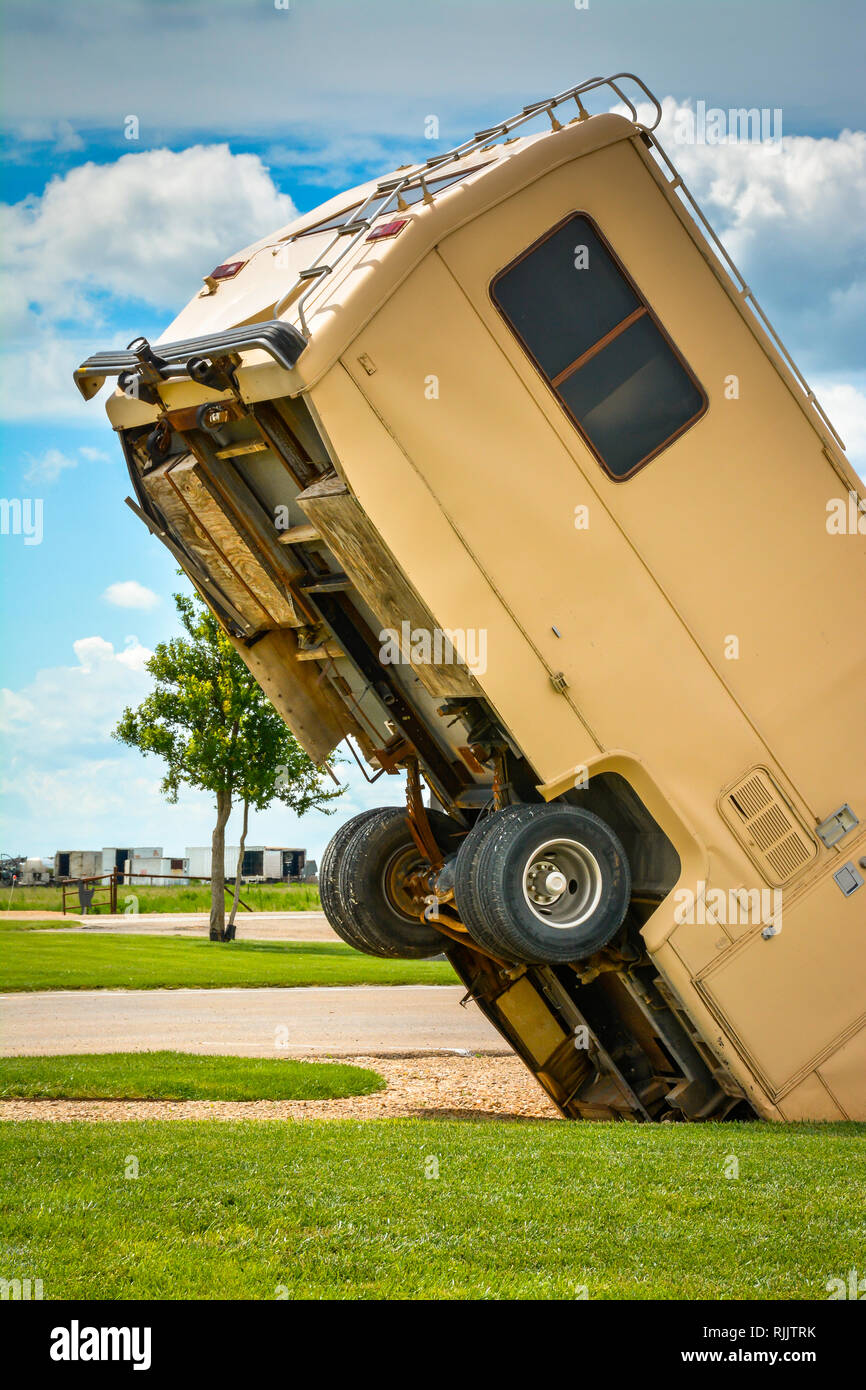 An unsettling view of an old RV buried nose first into the ground with back half of the RV lifted up towards the sky at a roadside attraction in TX - Stock Image