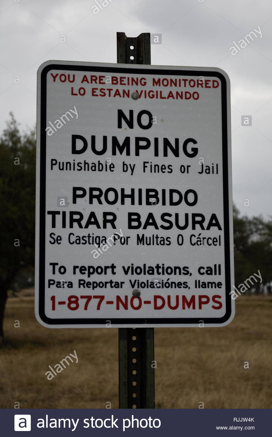 No Dumping Sign in English and Spanish. You are being monitored. No Dumping punishable by fines or jail. Texas. Dead Mans Hole No Dumping Sign Texas - Stock Image