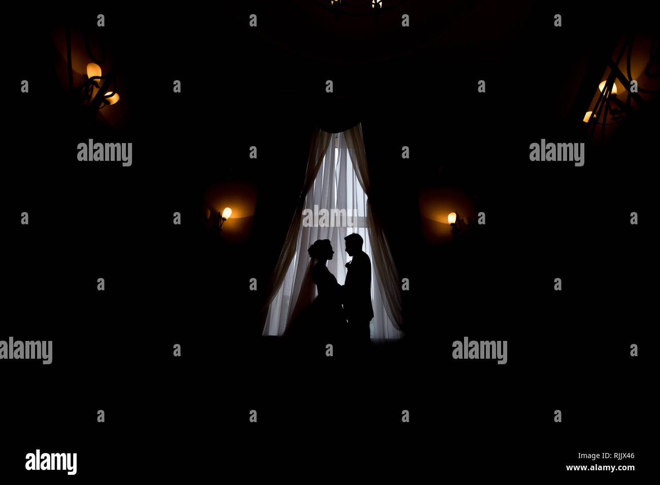 happy luxury bride and groom standing at window light in rich room, tender moment Stock Photo