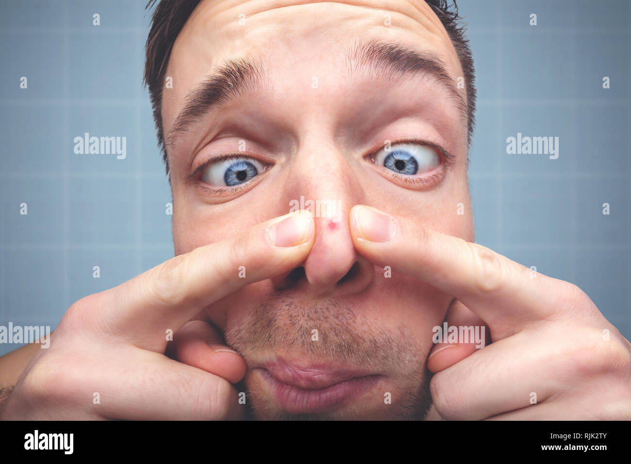 Funny portrait of a man with a pimple on the nose - Stock Image