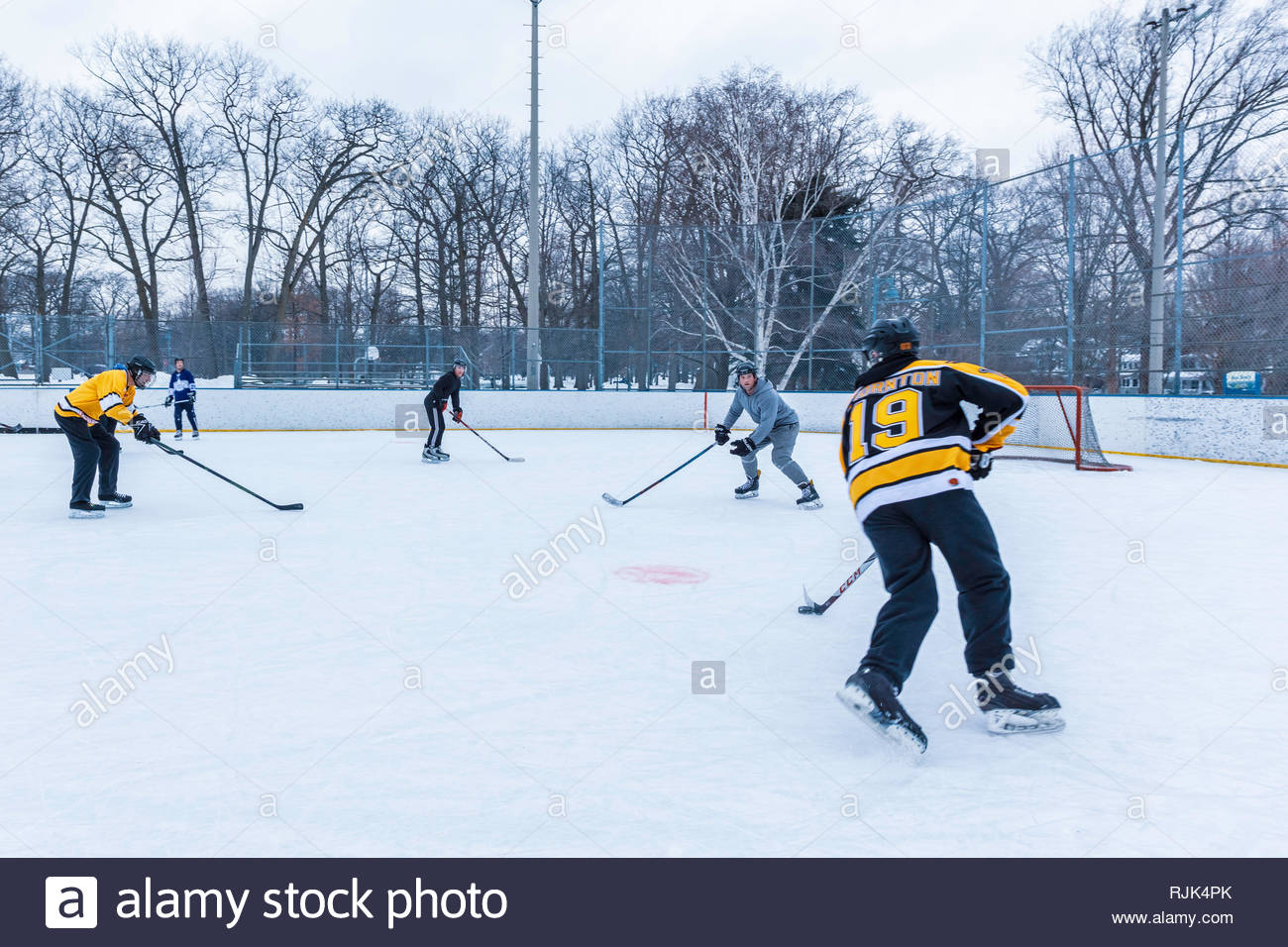 Shinney pickup ice hockey, Canada's national winter sport, on city rink in The Beaches area of Toronto Ontario Canada - Stock Image