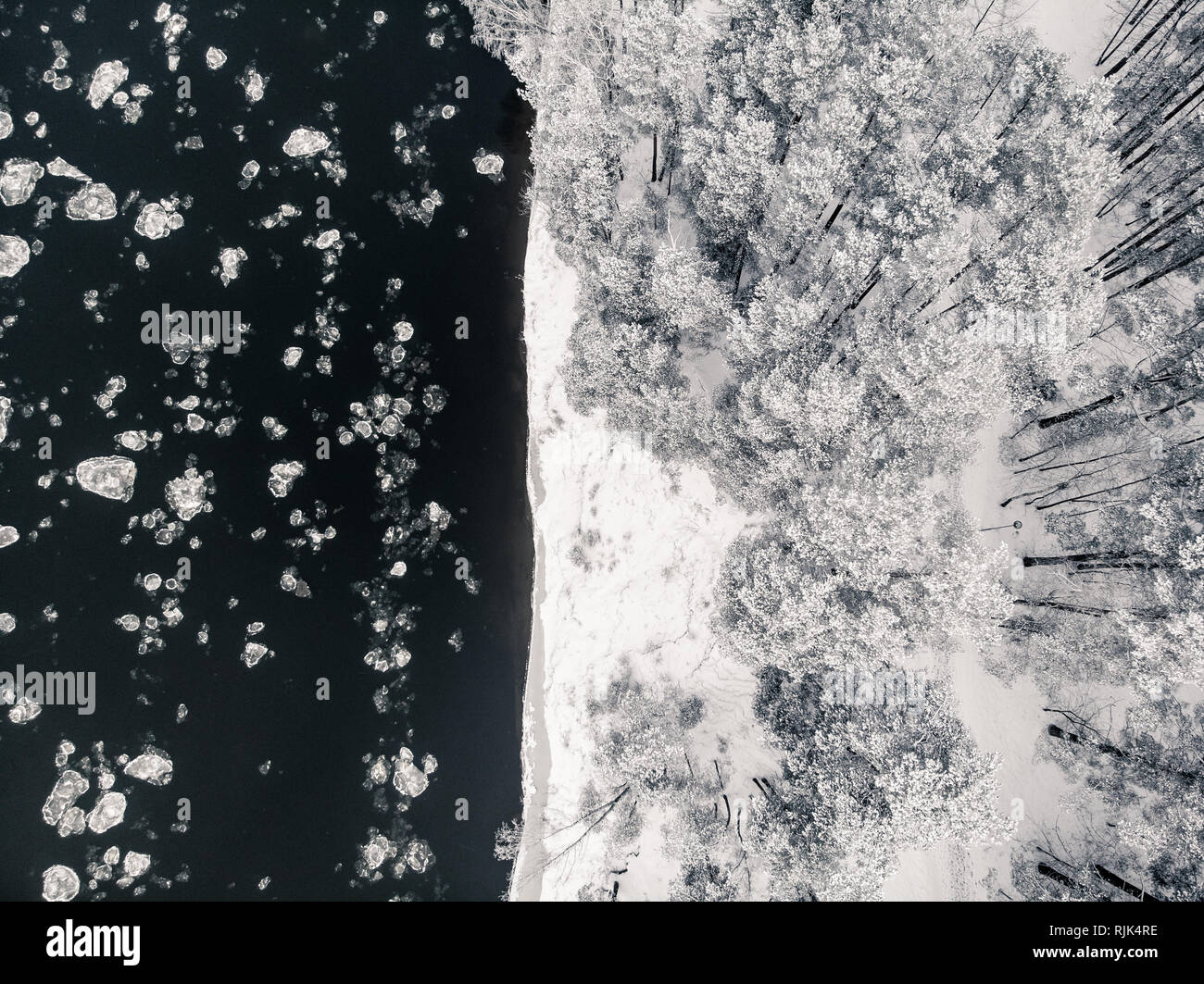 Birds eye view of freezing river and snowy forest from drone - Stock Image