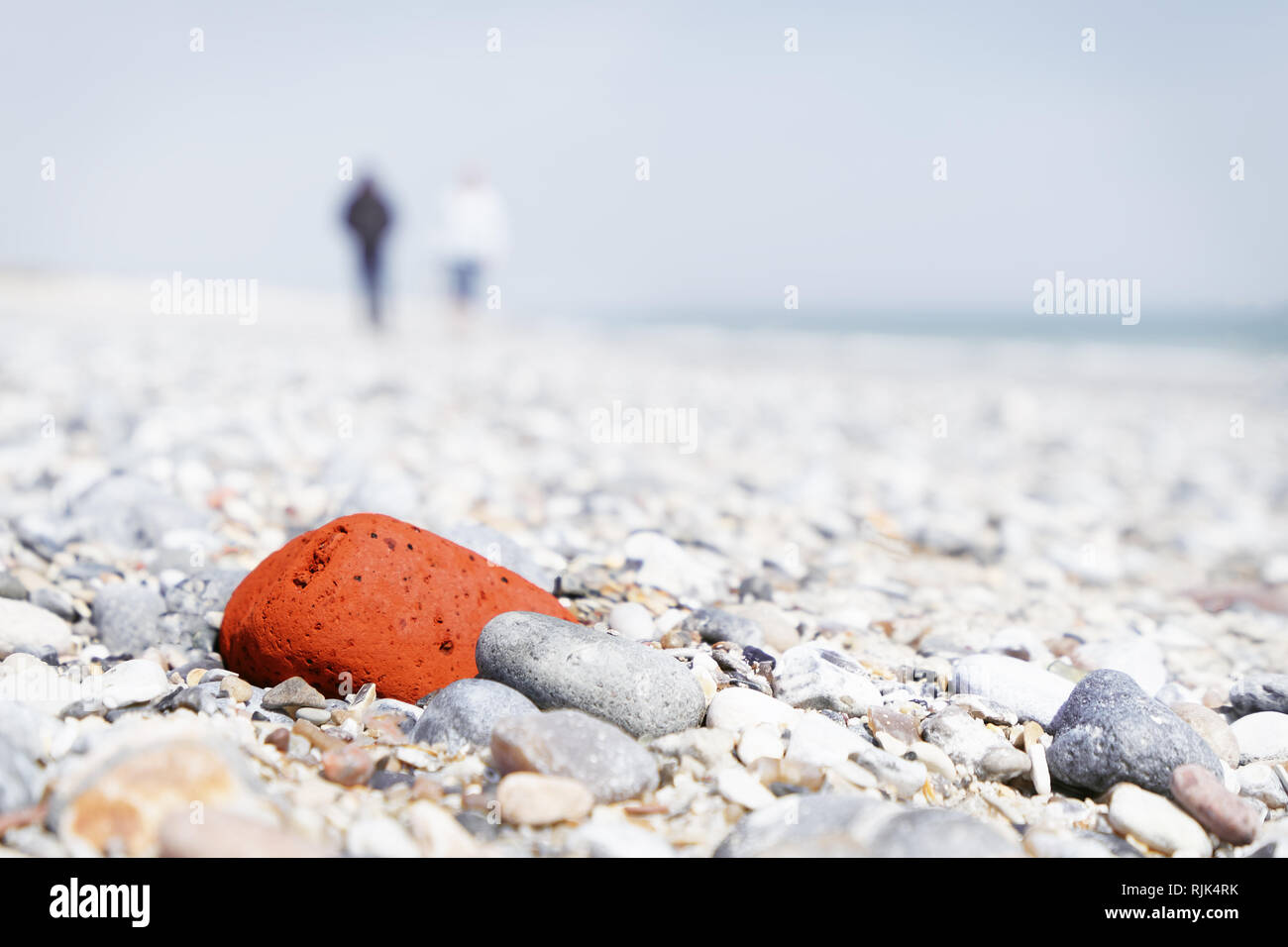Bright stone beach with a striking red stone in the focus area, behind it shadowy 2 people and the sea - close-up, perspective - Location: Germany, No - Stock Image