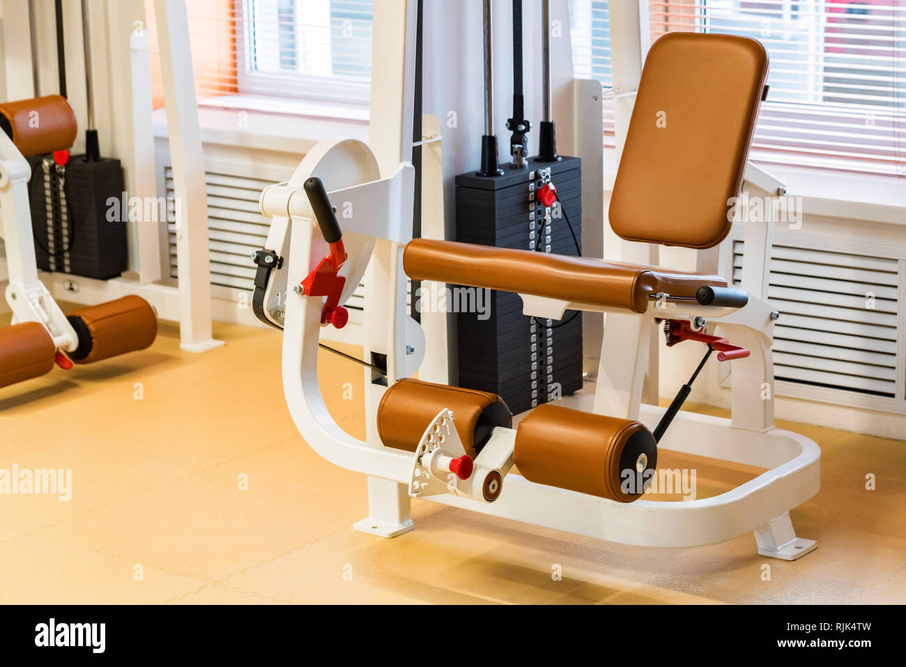 Empty leg extension exercise machine in modern gym - Stock Image