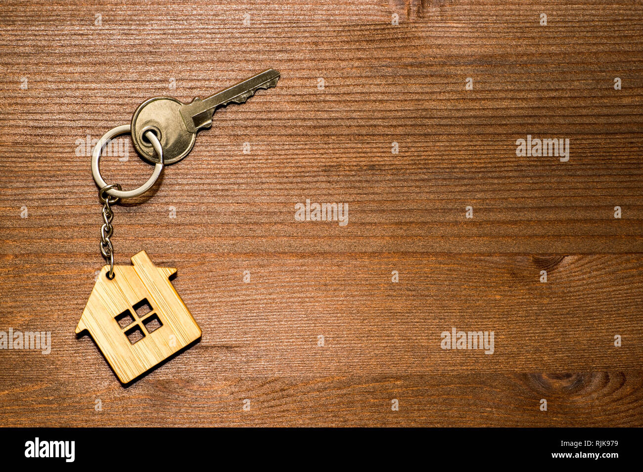 Symbol of a bamboo house with a metal key on a brown vintage wooden background. Lighting gradient. The concept of selling real estate with the transfe - Stock Image