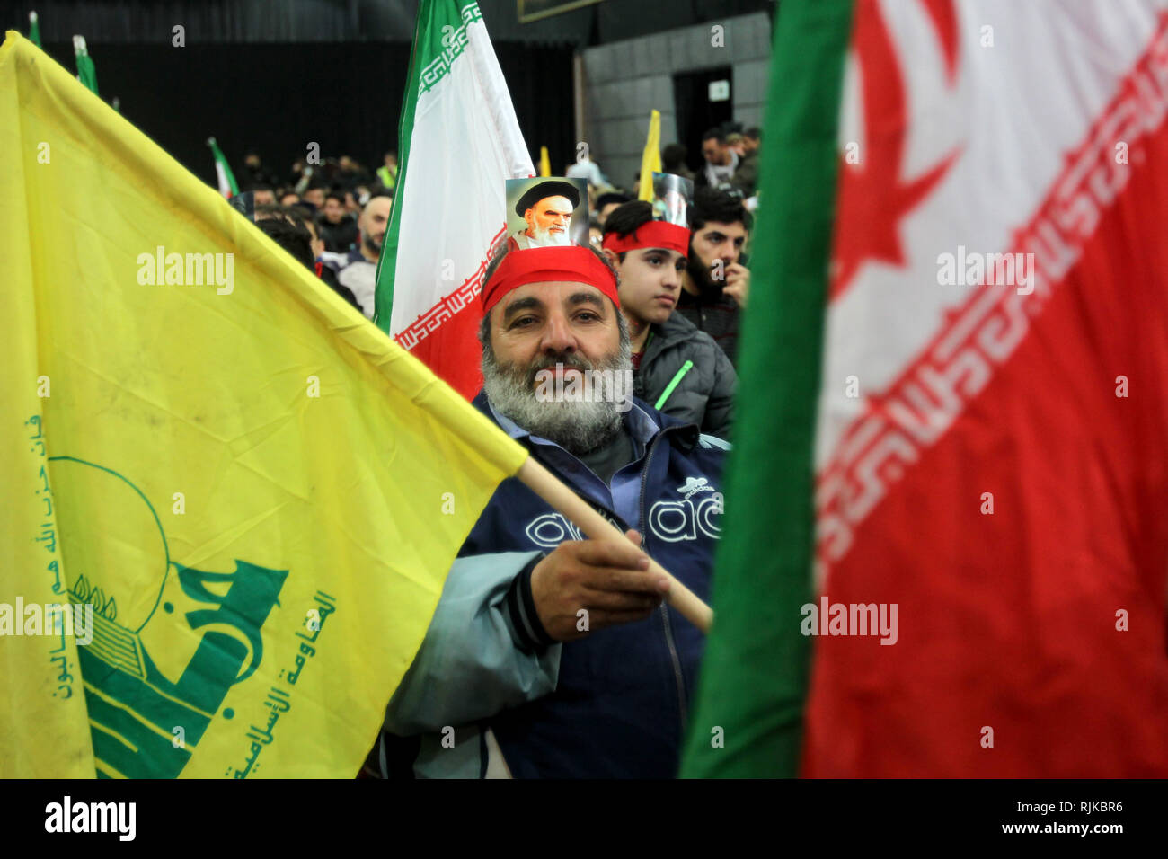 06 February 2019, Lebanon, Beirut: A man with a picture, strapped to his head, of Ayatollah Khomeini, former Supreme Leader of Iran and leader of the 1979 Iranian Revolution, takes part in a rally by supporters of Hezbollah, the pro-Iranian Lebanese Islamist political party and militant group, to mark the 40th anniversary of the Iranian Islamic Revolution which toppled Mohammad Reza Pahlavi, the last Shah of Iran. Photo: Marwan Naamani/dpa - Stock Image