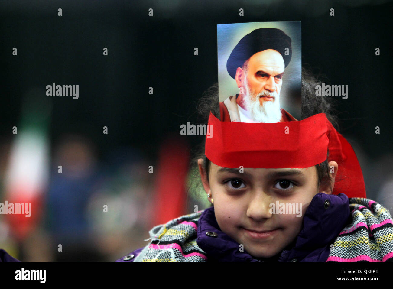 06 February 2019, Lebanon, Beirut: A girl with a picture, strapped to her head, of Ayatollah Khomeini, former Supreme Leader of Iran and leader of the 1979 Iranian Revolution, takes part in a rally by supporters of Hezbollah, the pro-Iranian Lebanese Islamist political party and militant group, to mark the 40th anniversary of the Iranian Islamic Revolution which toppled Mohammad Reza Pahlavi, the last Shah of Iran. Photo: Marwan Naamani/dpa - Stock Image