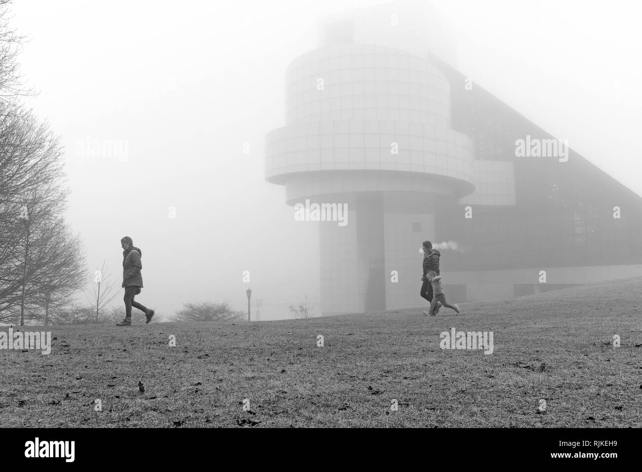 Cleveland, Ohio, USA. 6th Feb, 2019.  Three females cross fog shrouded greenspace next to the Cleveland Rock and Roll Hall of Fame and Museum along the North Coast Harbor in Cleveland, Ohio, USA. Credit: Mark Kanning/Alamy Live News. - Stock Image