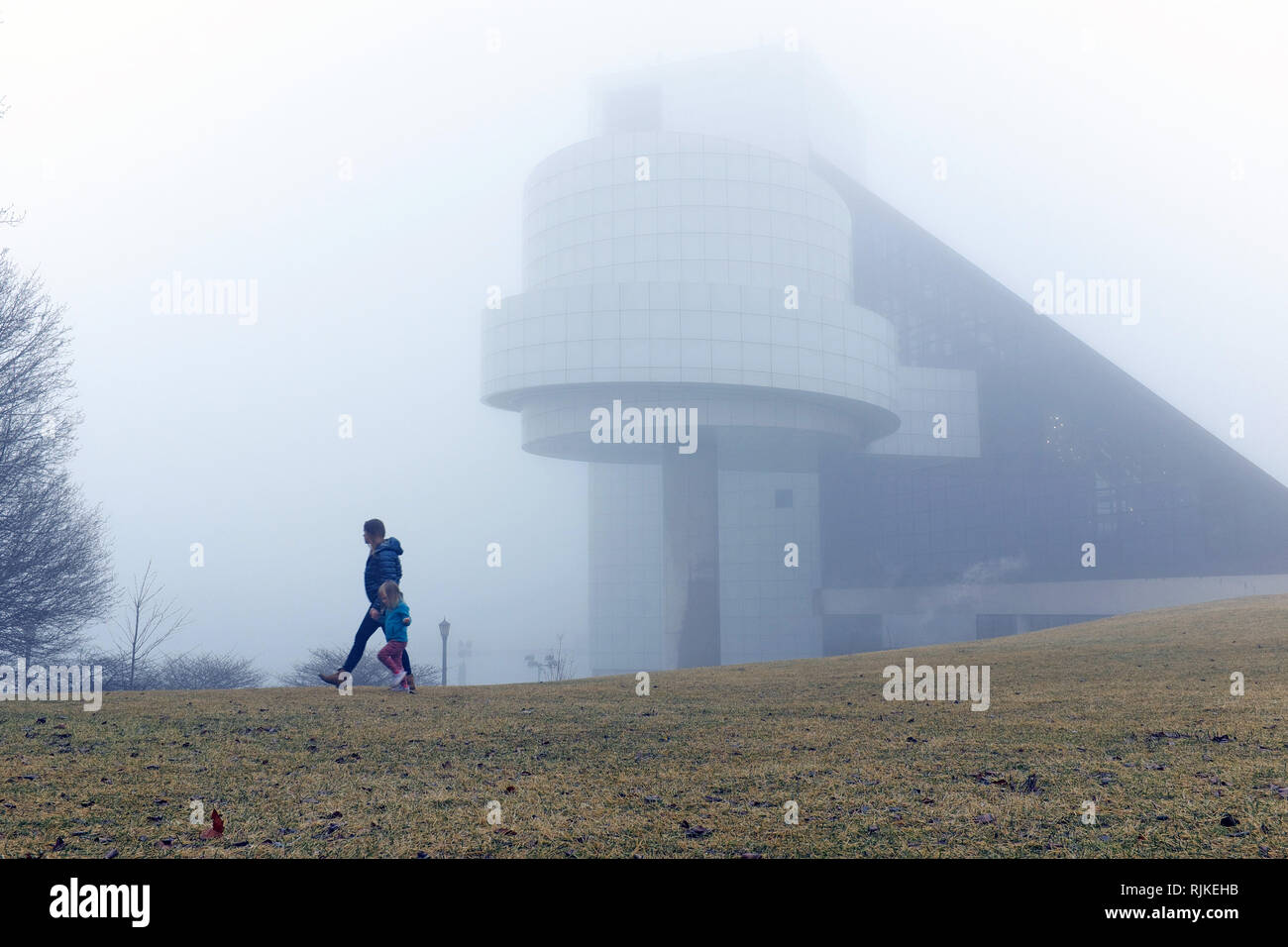 Cleveland, Ohio, USA. 6th Feb, 2019.  A woman and young girl stroll along the extremely foggy north coast harbor in downtown Cleveland, Ohio, USA.  The Rock and Roll Hall of Fame and Museum, designed by I.M Pei, takes on a surreal look during this extreme weather phenomena.  Credit: Mark Kanning/Alamy Live News. - Stock Image