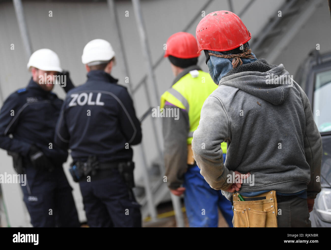 07 February 2019, Hessen, Frankfurt/Main: Customs officers inspect construction workers during a mission on a large construction site in the Niederrad district. The Special Unit Financial Control of Undeclared Work (FKS) takes action against illegal employment, minimum wage violations and social benefit abuse. Photo: Arne Dedert/dpa Stock Photo