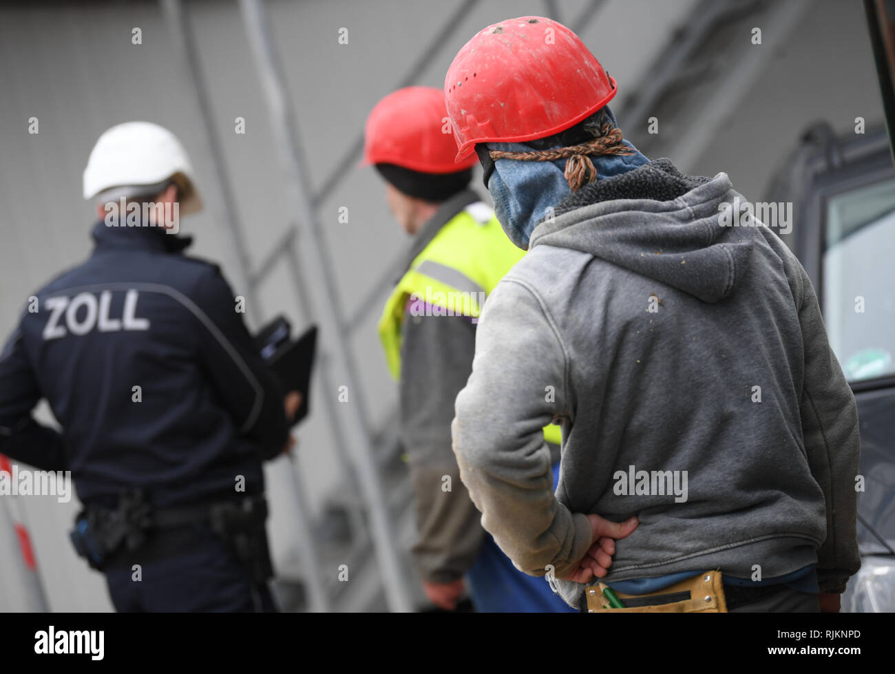 07 February 2019, Hessen, Frankfurt/Main: A customs official checks construction workers during a mission on a large construction site in the Niederrad district. The Special Unit Financial Control of Undeclared Work (FKS) takes action against illegal employment, minimum wage violations and social benefit abuse. Photo: Arne Dedert/dpa Stock Photo