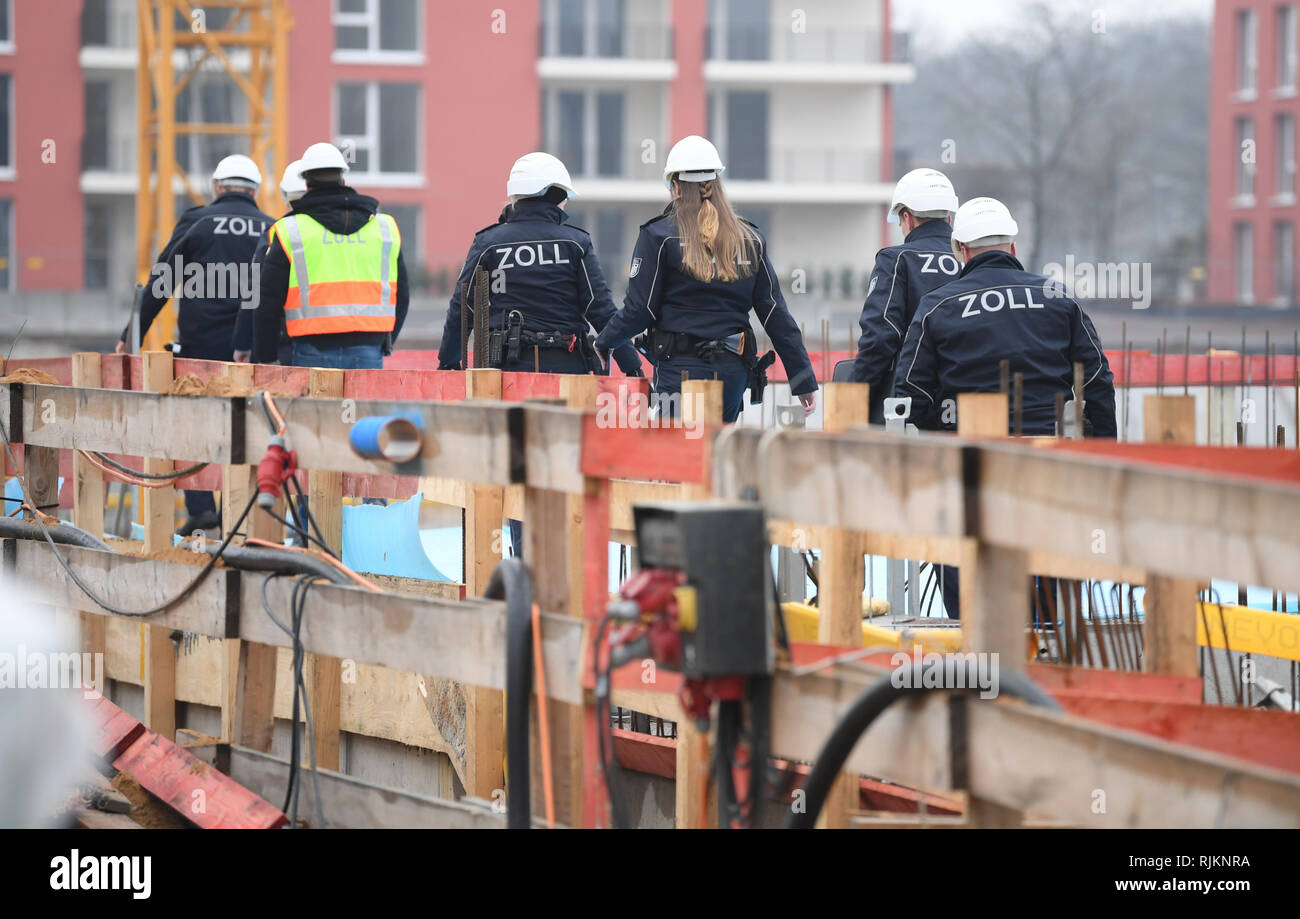 07 February 2019, Hessen, Frankfurt/Main: During a mission, customs officers walk across a large construction site in the Niederrad district. The Special Unit Financial Control of Undeclared Work (FKS) takes action against illegal employment, minimum wage violations and social benefit abuse. Photo: Arne Dedert/dpa Stock Photo
