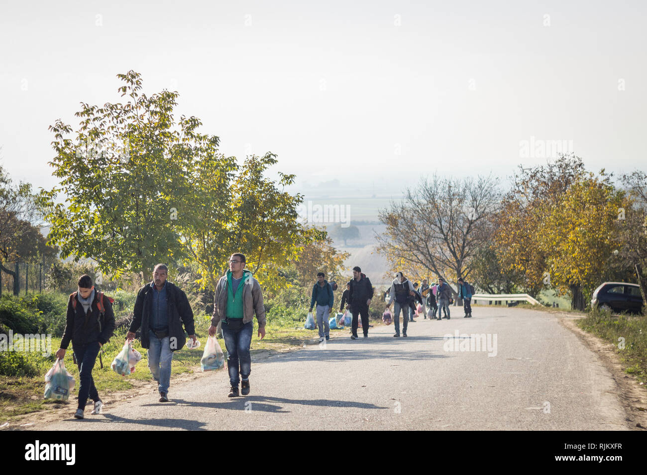 BERKASOVO, SERBIA - OCTOBER 17 2015: Refugees walking with heavy bags on the way to Croatia on the Croatian Serbian border, on the Balkans Route, duri - Stock Image