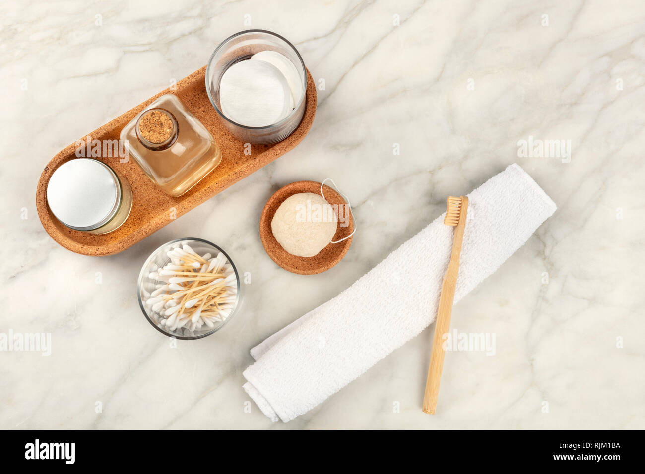 Sustainable toiletries. Homemade lotions, cotton pads, bamboo toothbrush, natural Konjac sponge, and biodegradable bamboo cotton swabs - Stock Image
