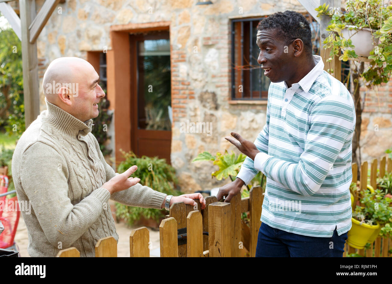 Two male farmers friendly talking outside next to wooden fence on background with brick house - Stock Image
