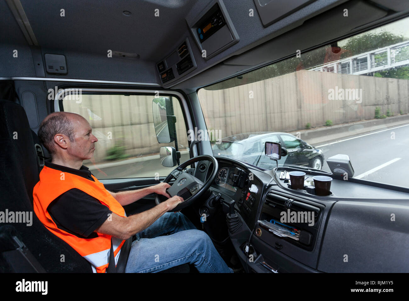 Driver in his truck during his tour Stock Photo