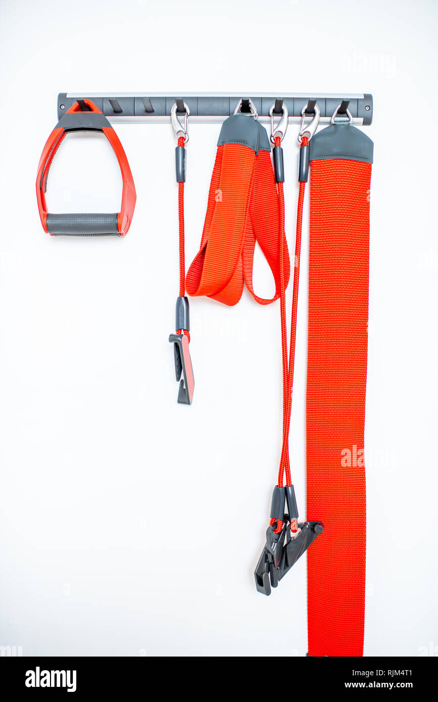 Red ropes and straps of the suspension medical equipment for spine treatment at the clinic - Stock Image