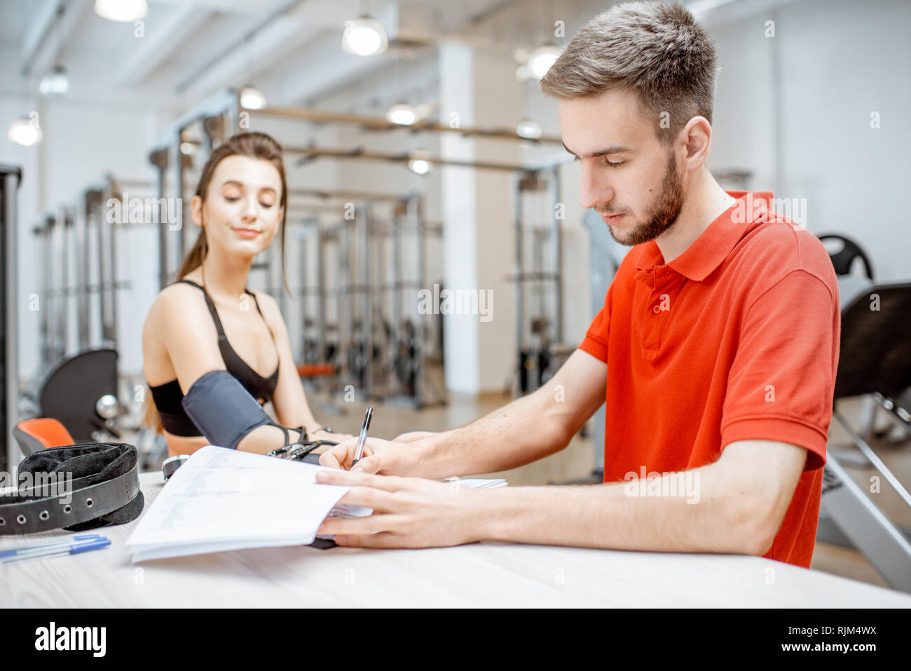 Man as a rehab in red uniform measuring pressure to a young woman sitting at the rehabilitation gym - Stock Image