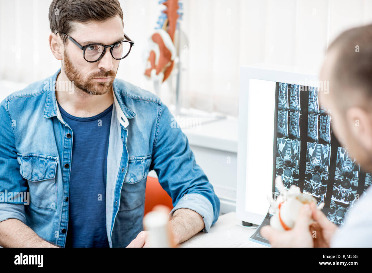 Man during the medical consultation with senior therapist looking on the vertebral model at the office - Stock Image