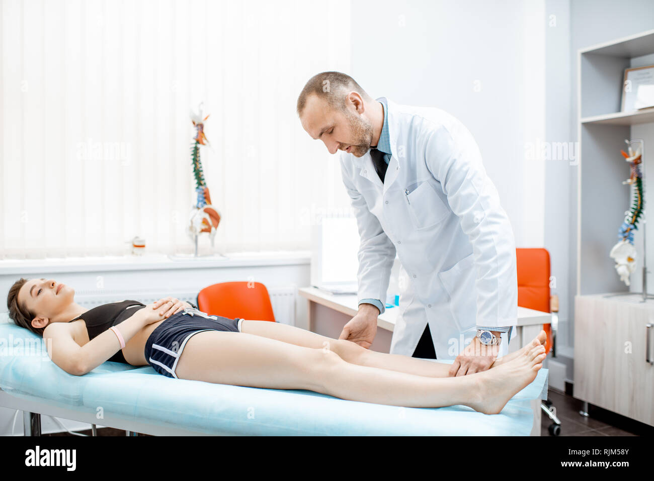 Woman lying on the medical couch during the examination with senior therapist in the office - Stock Image