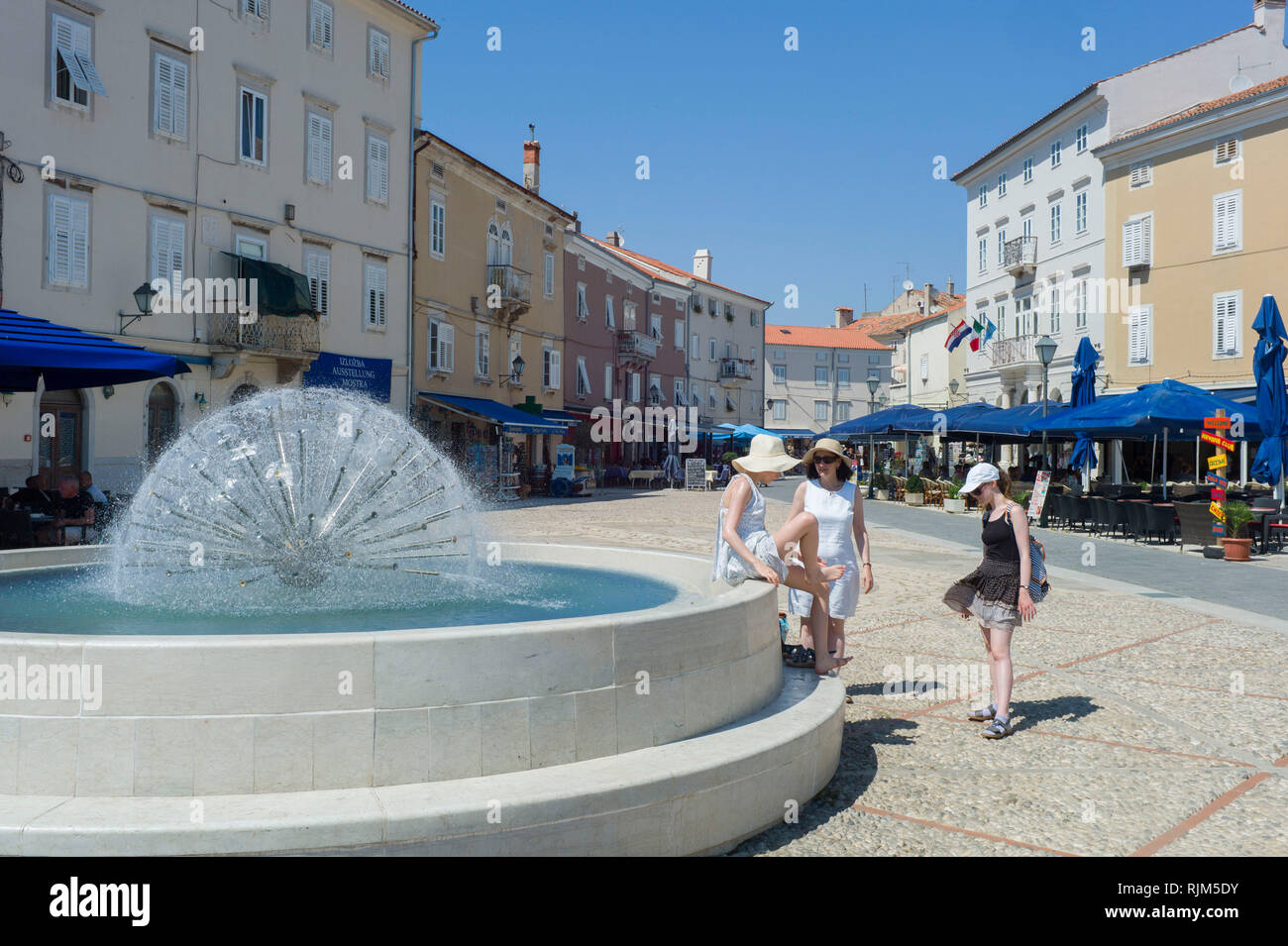 Cooling down on a hot day in the fountain in Cres Town, Cres Island, Croatia - Stock Image