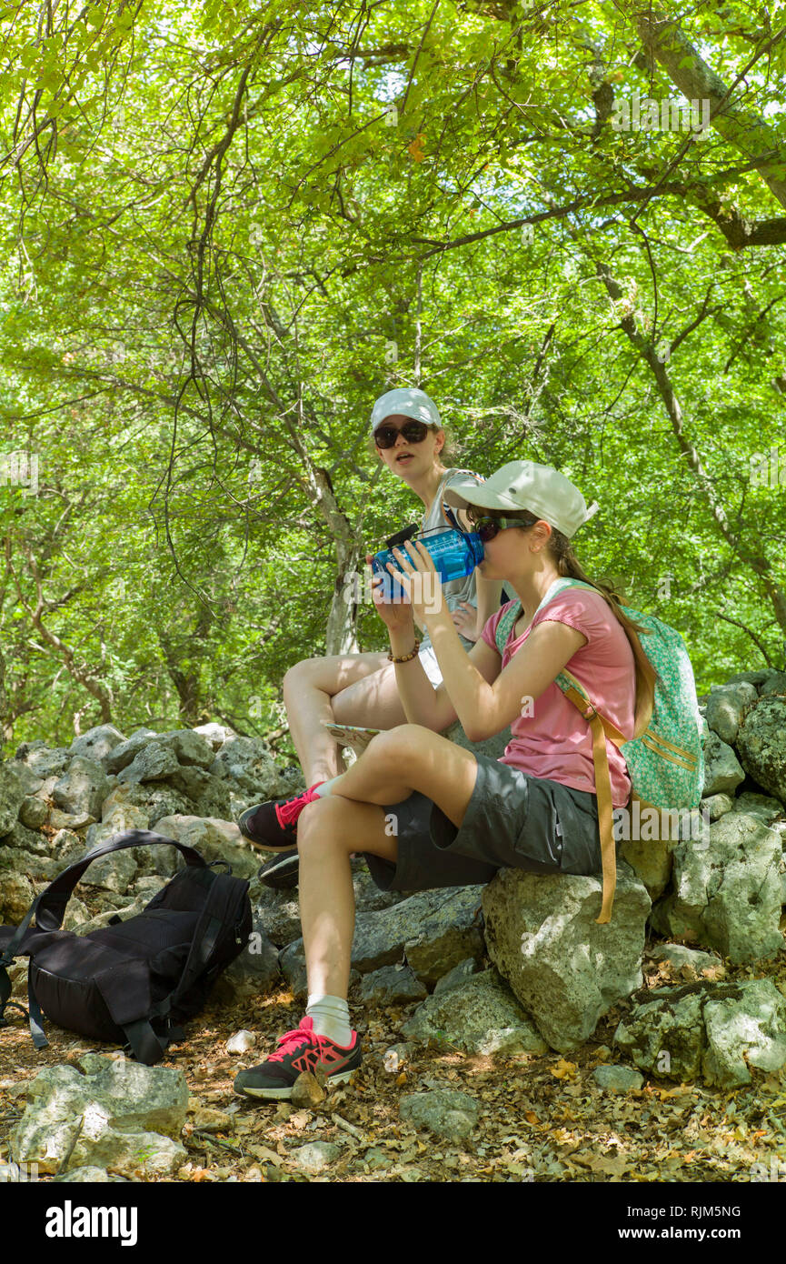 Two children stop for a drink on a very hot day in woodland near Porozina, Cres Island Croatia - Stock Image