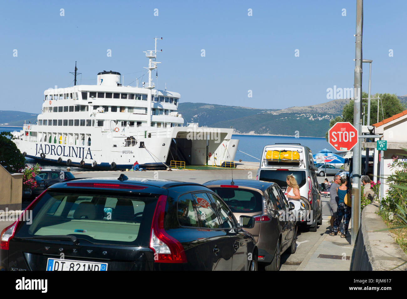 Car waiting for the ferry to take them to Brestova from Porozina on the island of Cres, Croatia - Stock Image