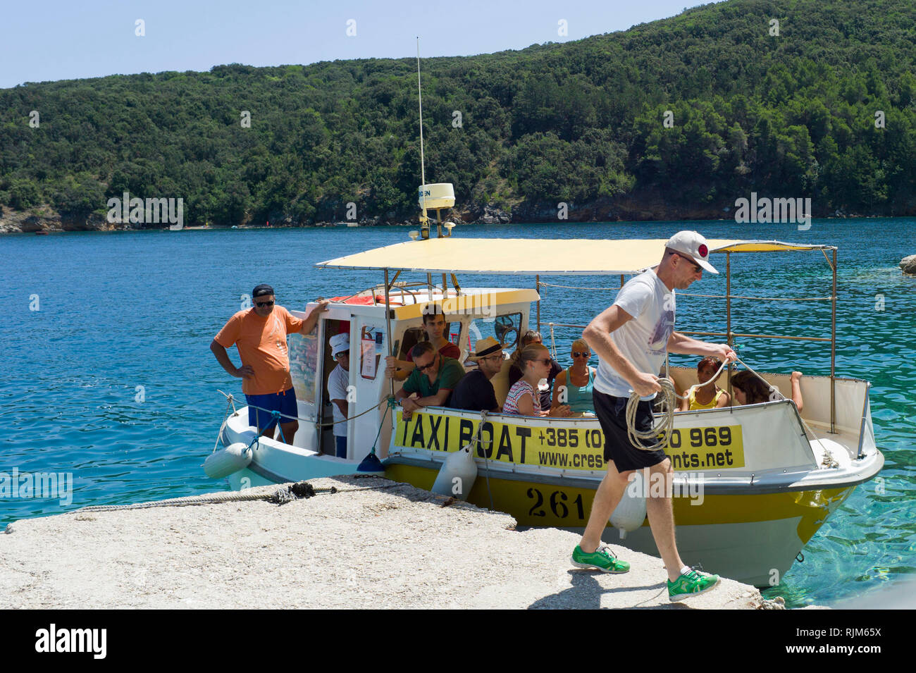 A small taxi boat ( ferry ) lands in the harbour of Valun village on the island of Cres Croatia Stock Photo