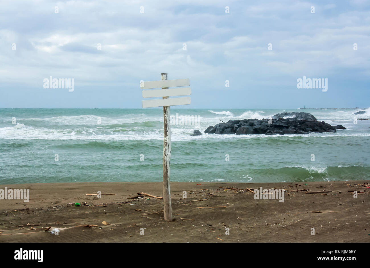 A blank sign in front of the sea on Fiumicino (Rome) sea. Sea waves bump into rocks. Beach shoot in a winter windy day. - Stock Image