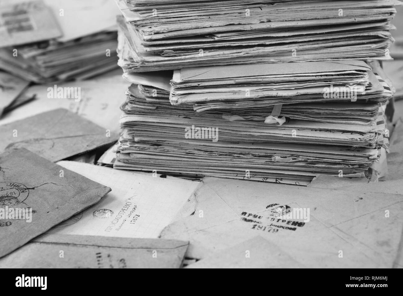 Pile of the old postal paper mails of 20 century in USSR. Envelopes are stamped: 'Viewed by military cencorship'. Black and white - Stock Image