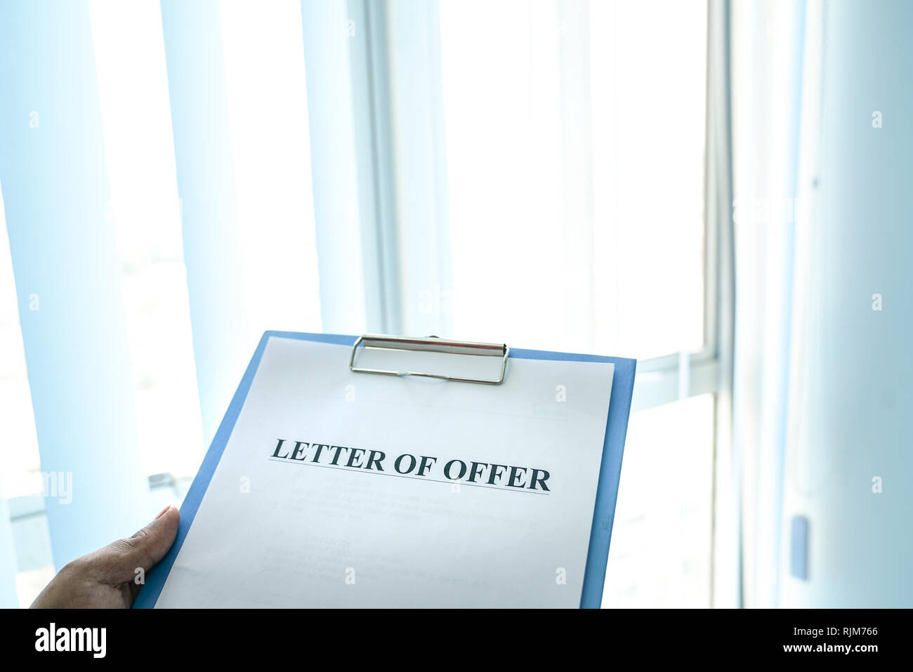 Hand holding letter of offer clipped on a board - Stock Image